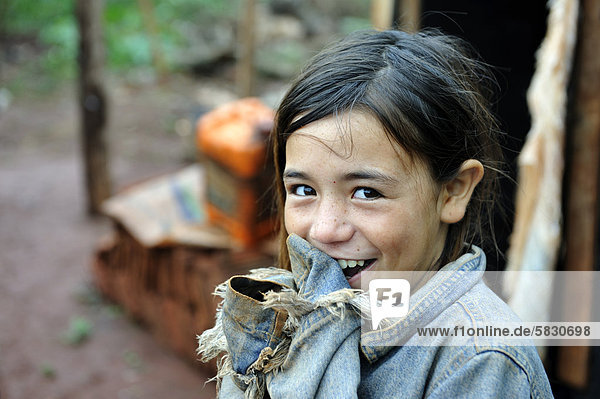 Portrait of a cheeky smiling girl  whose parents were forced off their land alongside dozens of other smallholders and their families by investors and now live in makeshift huts by the roadside  land grabbing  Carlos Antonio Lopez district  Itapua province  Paraguay  South America
