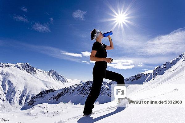 Skitourengeherin trinkt aus Flasche  Sonnenschein  Kühtai  Stubaier Alpen  Nordtirol  Tirol  Österreich  Europa