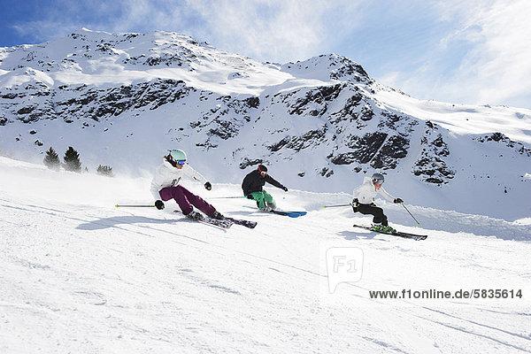 Skifahrer  die gemeinsam auf der Piste fahren