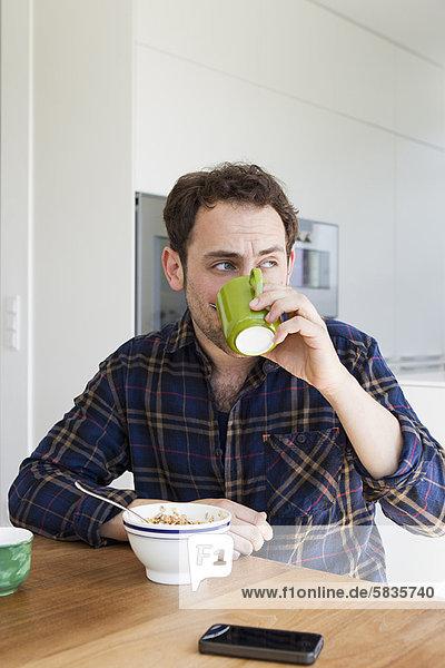 Mann beim Frühstück bei Tisch