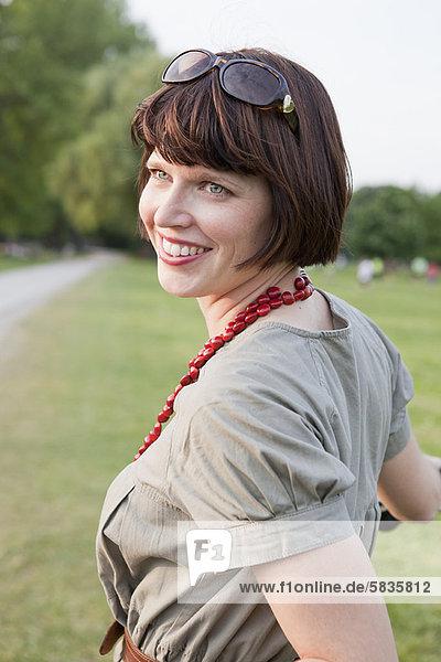 Lächelnde Frau im Feld stehend