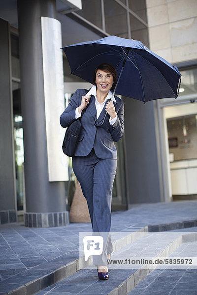 Businesswoman carrying umbrella outdoors