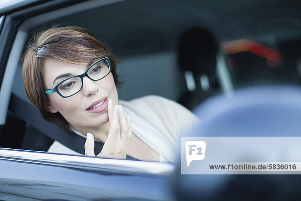 Woman checking makeup in side mirror