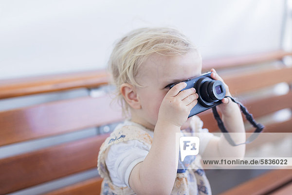 Toddler girl taking pictures with camera