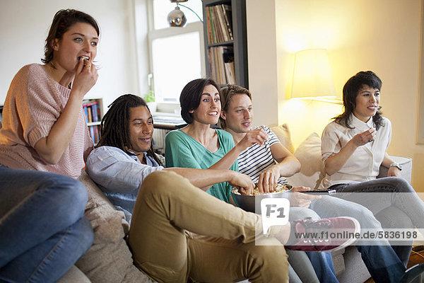 Freunde  die sich einen Film im Wohnzimmer anschauen