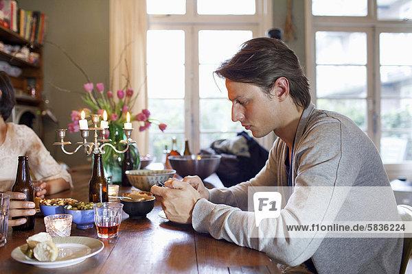 Mann mit Handy am Esstisch