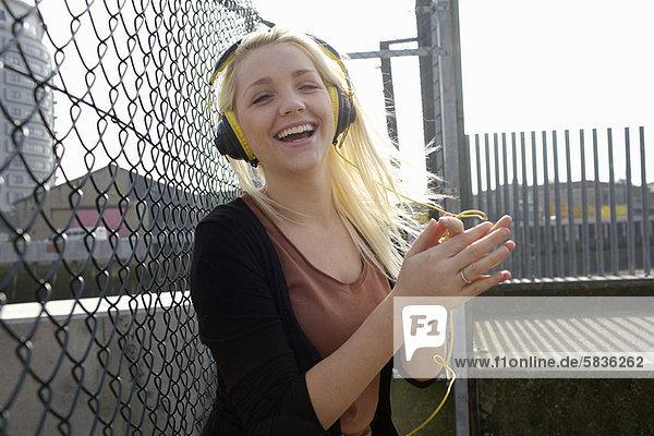 Lächelnde Frau beim Hören von Kopfhörern