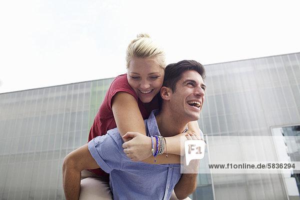 Mann mit Freundin Huckepack