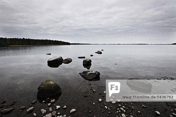 Bewölkter Himmel spiegelt sich im stillen See