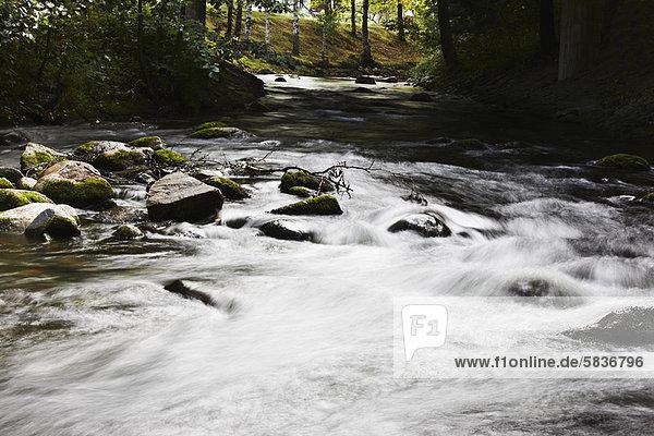 Verschwommener Blick auf den über Felsen rauschenden Fluss