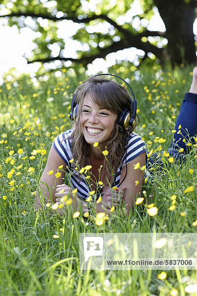 Frau hört Kopfhörer im Gras