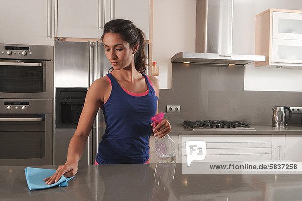 Frau reinigt Küchenarbeitsplatte