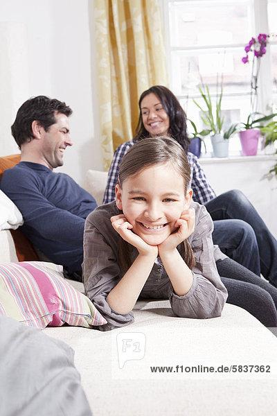Mädchen lächelnd auf Sofa im Wohnzimmer