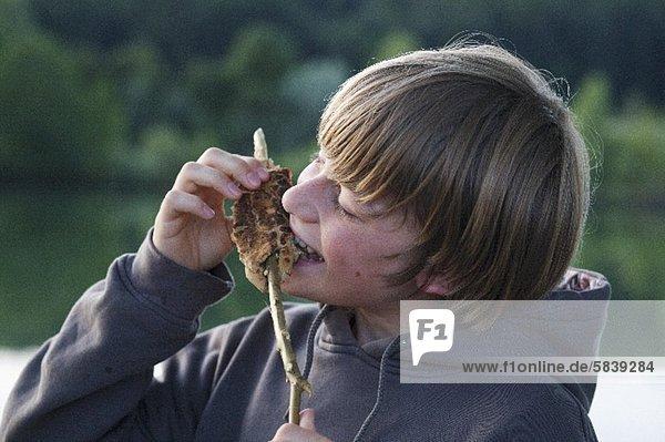 A boy eating stick bread