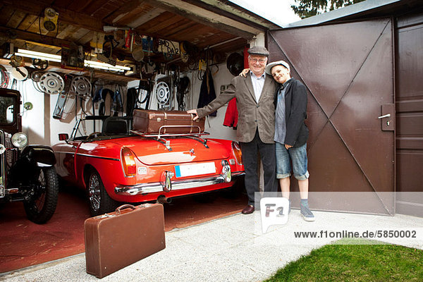 Großvater und Enkel mit Oldtimer und Koffer in der Garage