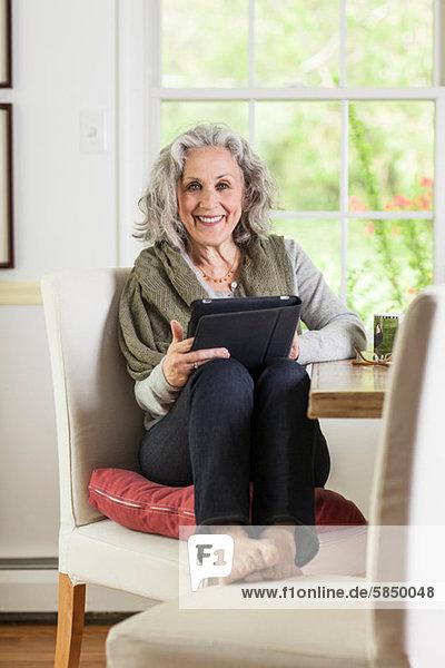 Seniorin mit digitalem Tablett zu Hause