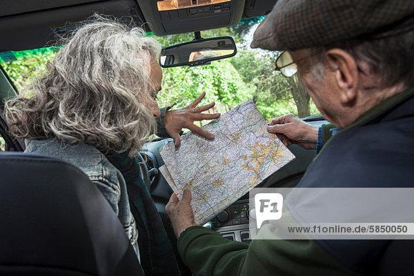 Seniorenpaar im Auto  Blick auf die Karte