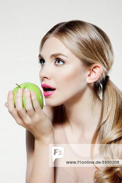 Junge Frau beim Apfelessen