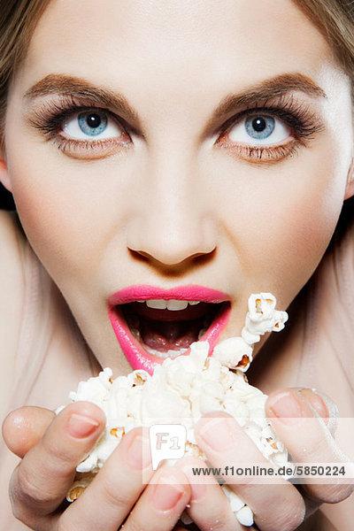 Junge Frau isst Popcorn