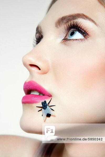 Junge Frau mit Plastikfliege im Gesicht