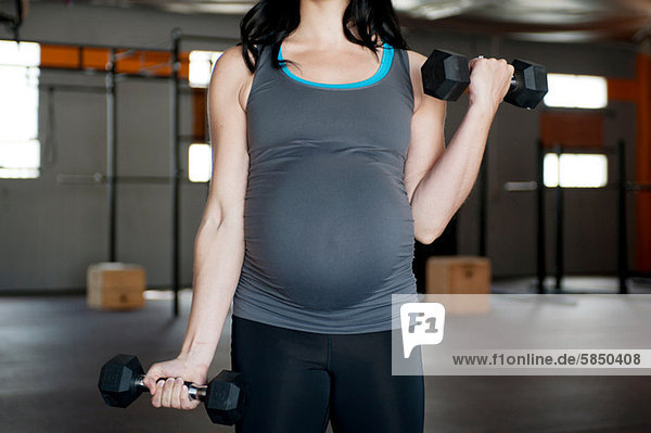 Pregnant young woman with hand weights