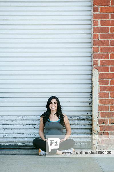 Schwangere junge Frau im Kreuzbein sitzend  Portrait