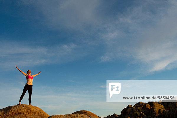 Junge Frau steht in der Wüste mit offenen Armen