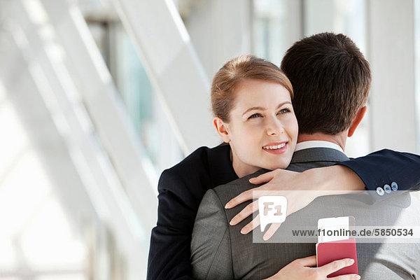 Geschäftsfrau und Geschäftsmann umarmend