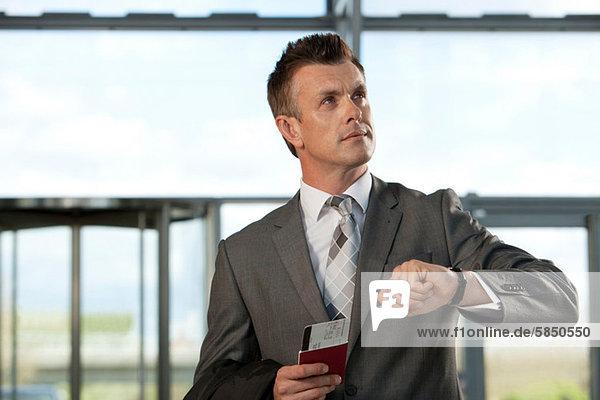 Geschäftsmann mit Flugticket und Passkontrolluhr