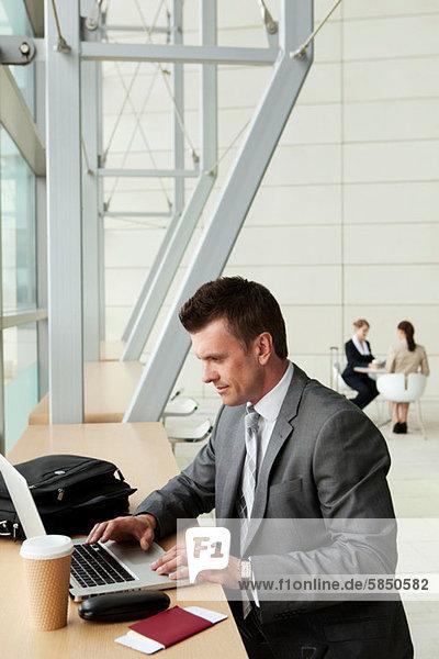 Geschäftsmann mit Laptop am Flughafen