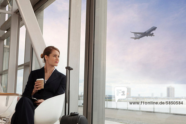 Geschäftsfrau trinkt Kaffee am Flughafen