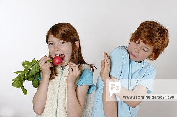 Mädchen isst Radieschen  Junge lehnt Rohkost ab