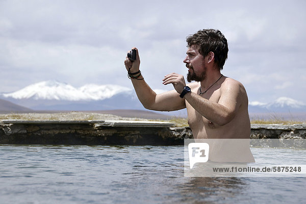 'Photographer standing in the hot springs at ''Laguna Verde'' on the Bolivian Altiplano  Bolivia  South America'