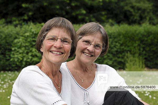 Zwei rüstige Zwillingsschwestern sitzen im Garten