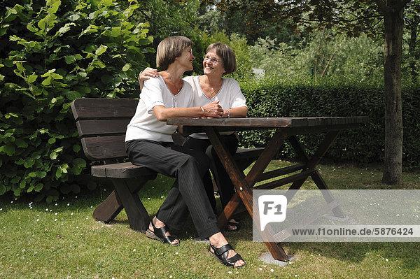 Zwei rüstige Zwillingsschwestern sitzen auf einer Gartenbank