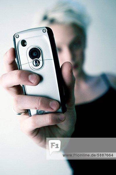 Close_up of a young woman taking a photograph with a mobile phone