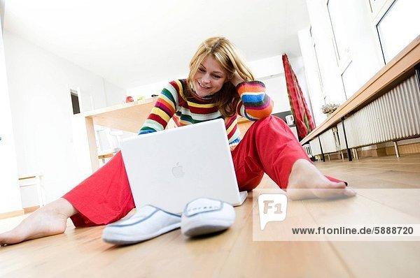 sitzend  benutzen  Frau  Boden  Fußboden  Fußböden  Notebook  jung