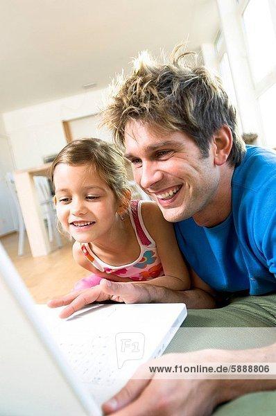 nebeneinander  neben  Seite an Seite  benutzen  Notebook  Menschlicher Vater  Tochter