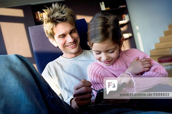 Father using a personal data assistant with his daughter