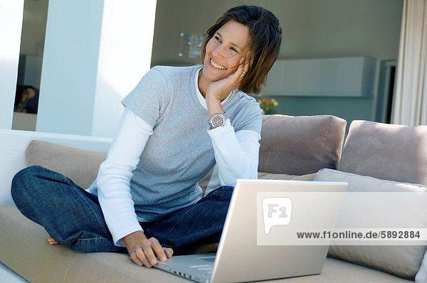 sitzend  Frau  lächeln  reifer Erwachsene  reife Erwachsene  Couch