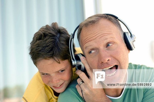 hinter Mann zuhören lächeln Sohn Kopfhörer Musik reifer Erwachsene reife Erwachsene Kleidung Klassisches Konzert Klassik
