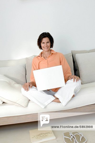 sitzend  Portrait  Frau  Notebook  auf dem Schoß sitzen  Mittelpunkt  Couch  Erwachsener