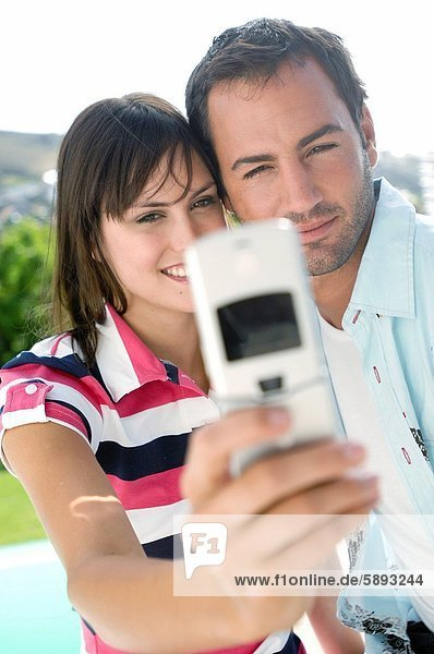 Young couple taking a picture of themselves with a mobile phone