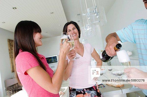 Frau  Mann  junger Erwachsener  junge Erwachsene  eingießen  einschenken  halten  Mittelpunkt  jung  Erwachsener  Champagner
