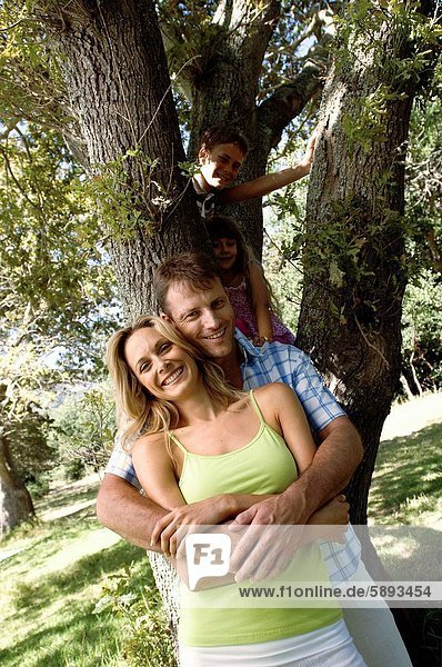 Mid adult man embracing a mid adult woman from behind with their children climbing a tree