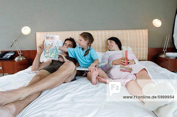 liegend  liegen  liegt  liegendes  liegender  liegende  daliegen  Buch  halten  Bett  Mittelpunkt  Tochter  Erwachsener