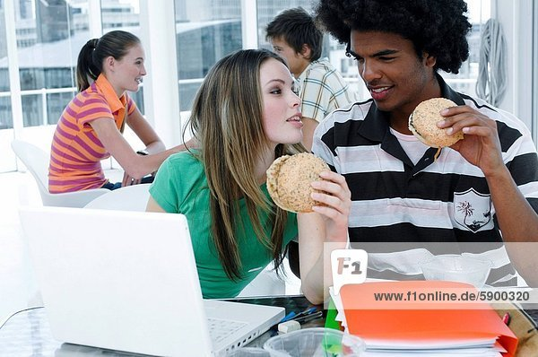Close_up of a young couple sitting in front of a laptop and holding burgers