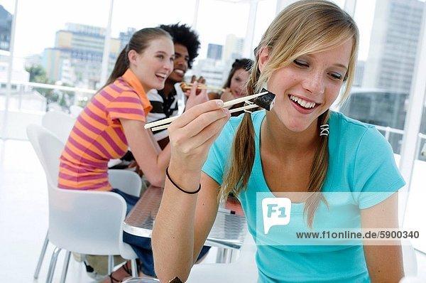 sitzend  Frau  Freundschaft  Eßstäbchen  Hintergrund  jung  essen  essend  isst