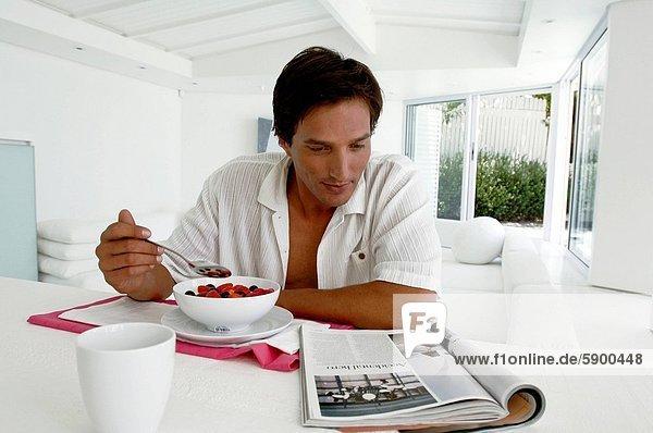Mann  am Tisch essen  Zeitschrift  Mittelpunkt  Tisch  Erwachsener  Frühstück  vorlesen