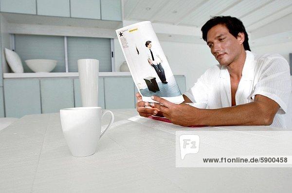 sitzend  Mann  am Tisch essen  Zeitschrift  Mittelpunkt  Tisch  Erwachsener  vorlesen